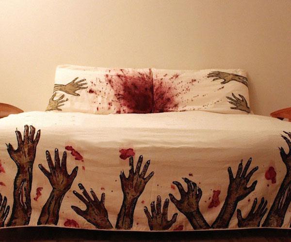 Observamos un tendido de cama  con grabados en la parte de abajo de man  os  en posición arriba en colores verdes y rojizo y almohada con estampados en en estos mismos colores