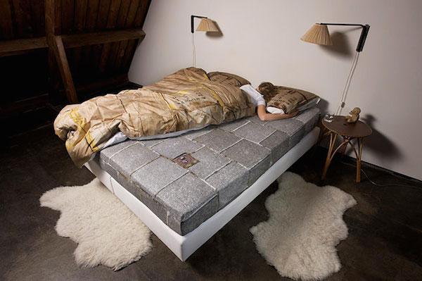 Vemos una cama con un persona dentro de un edredon y al lado otra persona que no se su cabeza en el suelo hay pequeños pedazos de pieles de animales en blanco