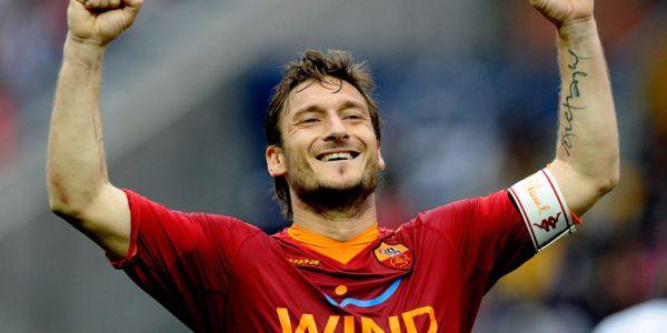 Vemos aquí a jugador de fútbol con uniforme rojo que sonríe y levanta sus  dos brazos  en señal de trinfo